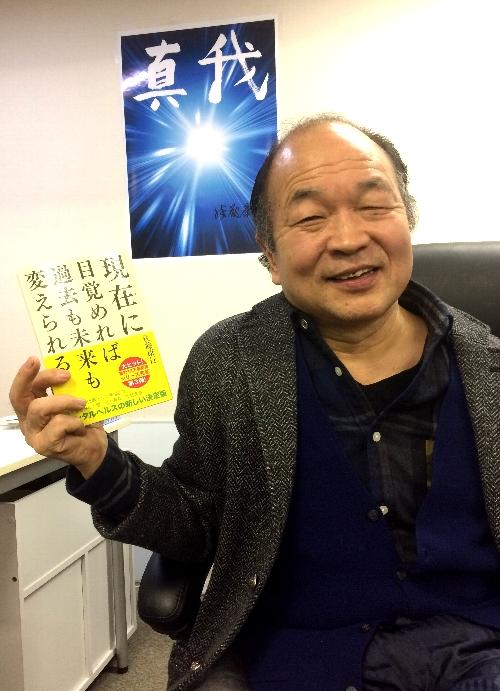 新刊を手にする佐藤康行先生